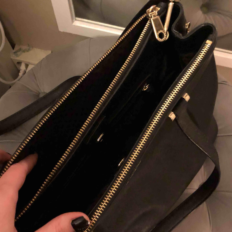 Äkta DKNY väska. Fem fack varan 3st större och 2 mindre med dragkedja inne i väskan. Knappt använd och o nyskick. Dustbag medföljer. Avtagbar axelrem. Accessoarer.