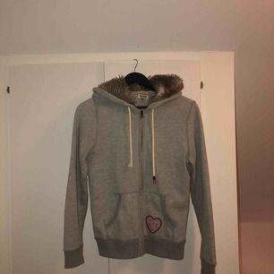 Jättefin hoodie med dragkedja framtill från Hilfiger Denim. Köpt på Tommy Hilfiger i Stockholm för 1300kr. Jätteskön luva med foder (fuskpäls). Jättefint skick, ena snöret är dock skadat (sista bilden)