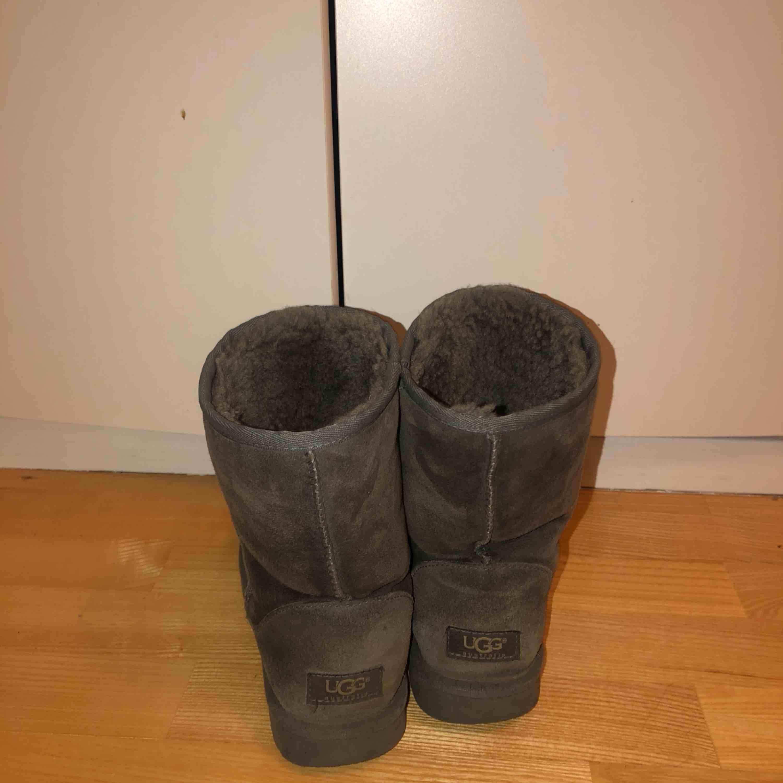 Gråa mellan höga Ugg skor. Använda, men fortfarande användbara! . Skor.