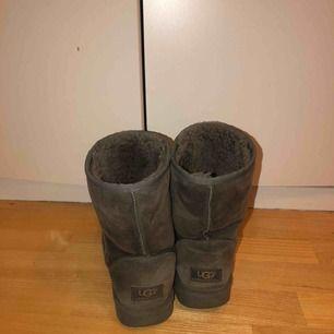 Gråa mellan höga Ugg skor. Använda, men fortfarande användbara!