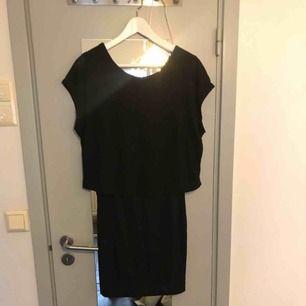 Svart kort tight klänning med en överdel som är som en lösare T-shirt med djup rygg. Använd max 3 ggr.