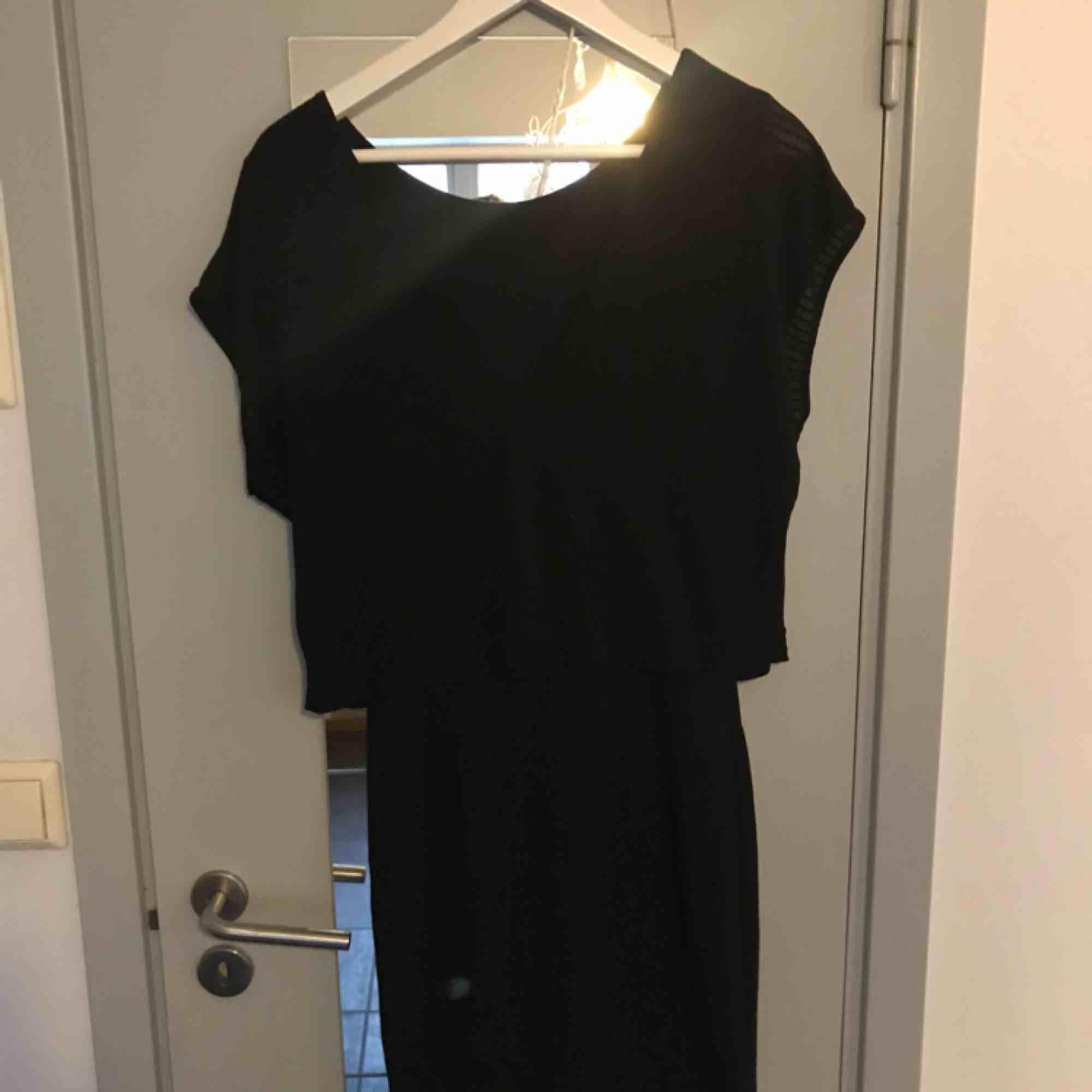 Svart kort tight klänning med en överdel som är som en lösare T-shirt med djup rygg. Använd max 3 ggr. . Klänningar.