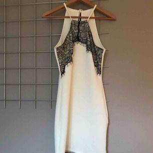 Kort vit klänning i halterneck-liknande modell med svart spets framtill. Endast använd 1 gång. Passar storlek XS/S.