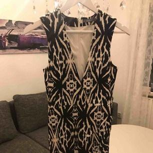 Oanvänd stilig klänning. Snygg tight passform med dragkedja i ryggen.