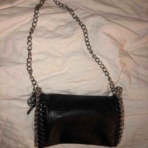 Säljer en svart väska från scorett, med silver/metal band.