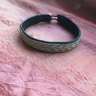 Tennkonstarmband med svart läder på insidan. Knapp i renhorn.  Minns ej var armbandet är inköpt.