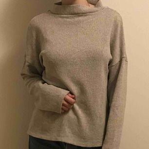Beige stickad tröja, ska egentligen ha urrigningen fram men tycker den är snyggare åt andra hållet, funkar på båda sätt:)