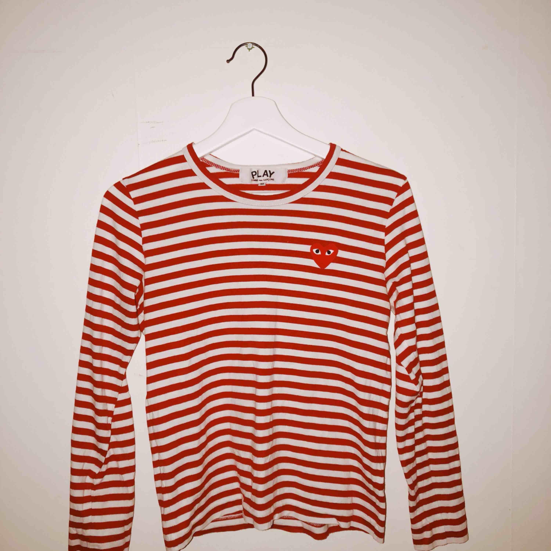 Snygg och ball tröja från Comme des garcons PLAY. Tröjan är i storlek M men jag skulle säga att den är en S. Den är i väldigt bra skick. Säljer pga att den är för liten för mig😭  Skulle nog kunna tänka mig att gå ner lite i pris vid snabb affär❤️❤️❤️. T-shirts.
