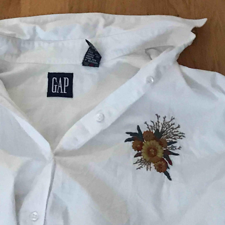 Skjortan från GAP med broderad detalj på bröstet. Jättefin! Aldrig använd.  Eventuell frakt betalas av köparen.. Skjortor.