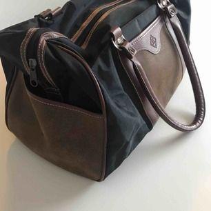 Snygg vintageväska med två små fack på utsidan och ett med dragkedja på insidan. Kan skicka fler bilder om så önskas. 43 cm lång och 22 cm hög!