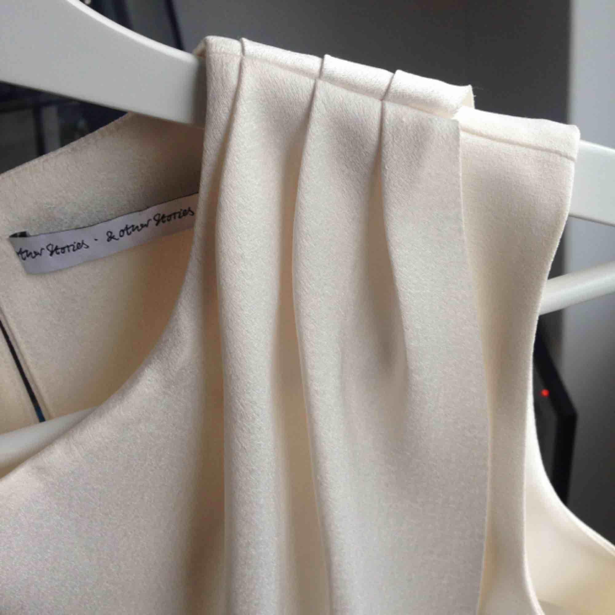 Gräddvit blus från & other stories, storlek 36. Lite glänsande tyg i draperingen fram, något mattare tyg i övrigt. Använd 2-3 gånger. . Blusar.