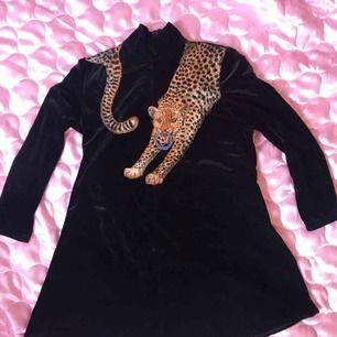 Vintage 80tals fynd, svart sammetsklänning med tiger på och små slitsar i sidan. Storlek M. Swisha 180:- så skickar jag via post asap! (Frakt ingår)