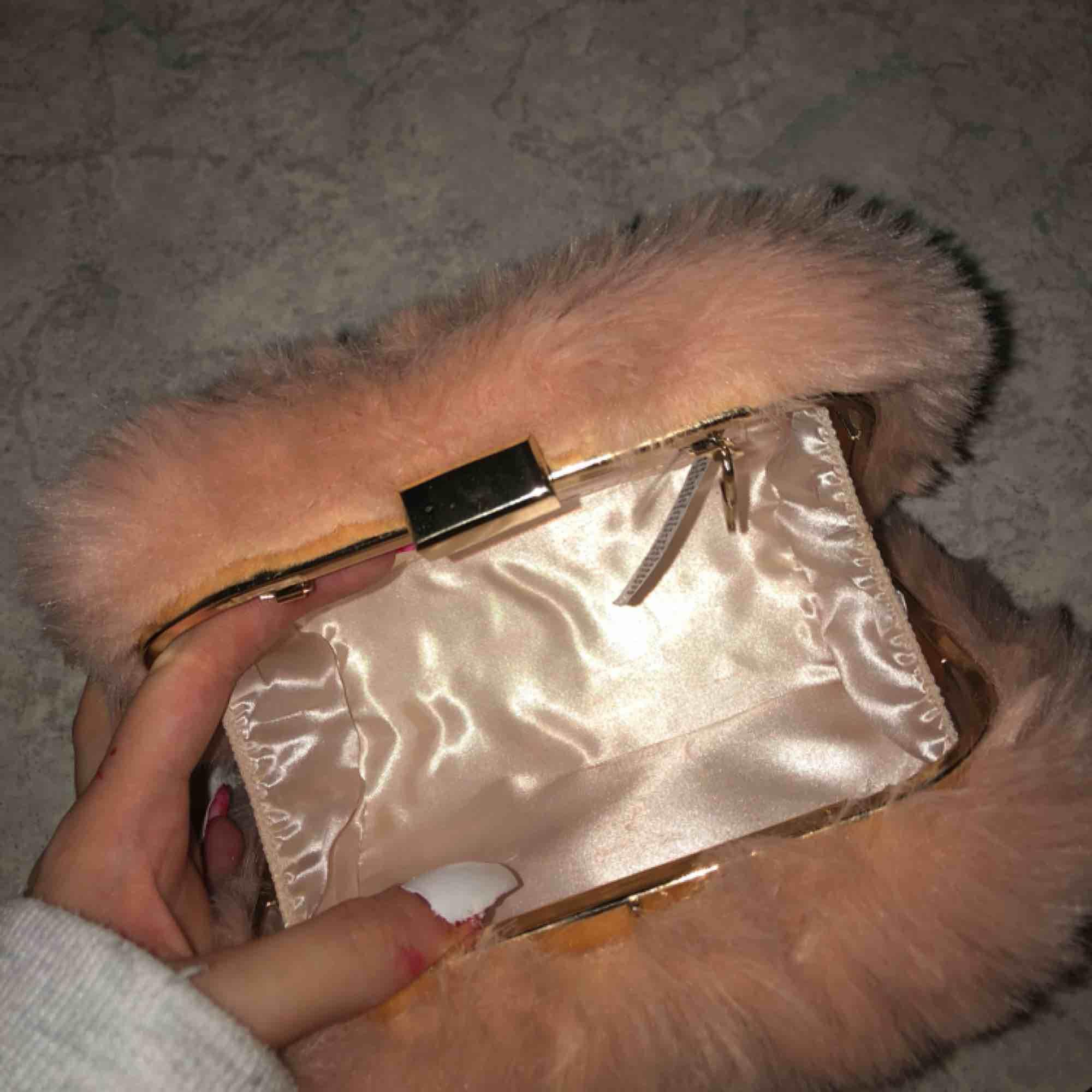 Clutch från New look i puderrosa fuskpäls. Satintyg på insidan, rymmer mobil, smink, borste osv. Har funnits en guldkedja till men den har lossnat därav priset. Köpt i London! . Väskor.