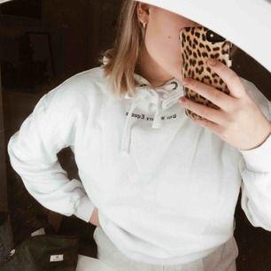 """Vit hoodie där det på bröstet står """"the future equals"""" och på luvan """"female"""". Väldigt fräsch!"""