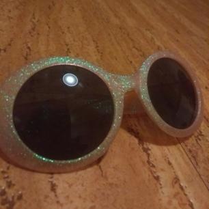 Rosa solglasögon med grönt skimrande glitter på, använda men i fint skick!