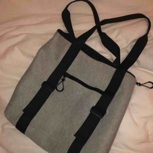 Grå väska från gina tricot av häftigt mjukis material. Endast använd två gånger och är helt i ny skick. Har ett ytterfack, ett stort fack och ett mindre innerfack. Köpt för 349kr.