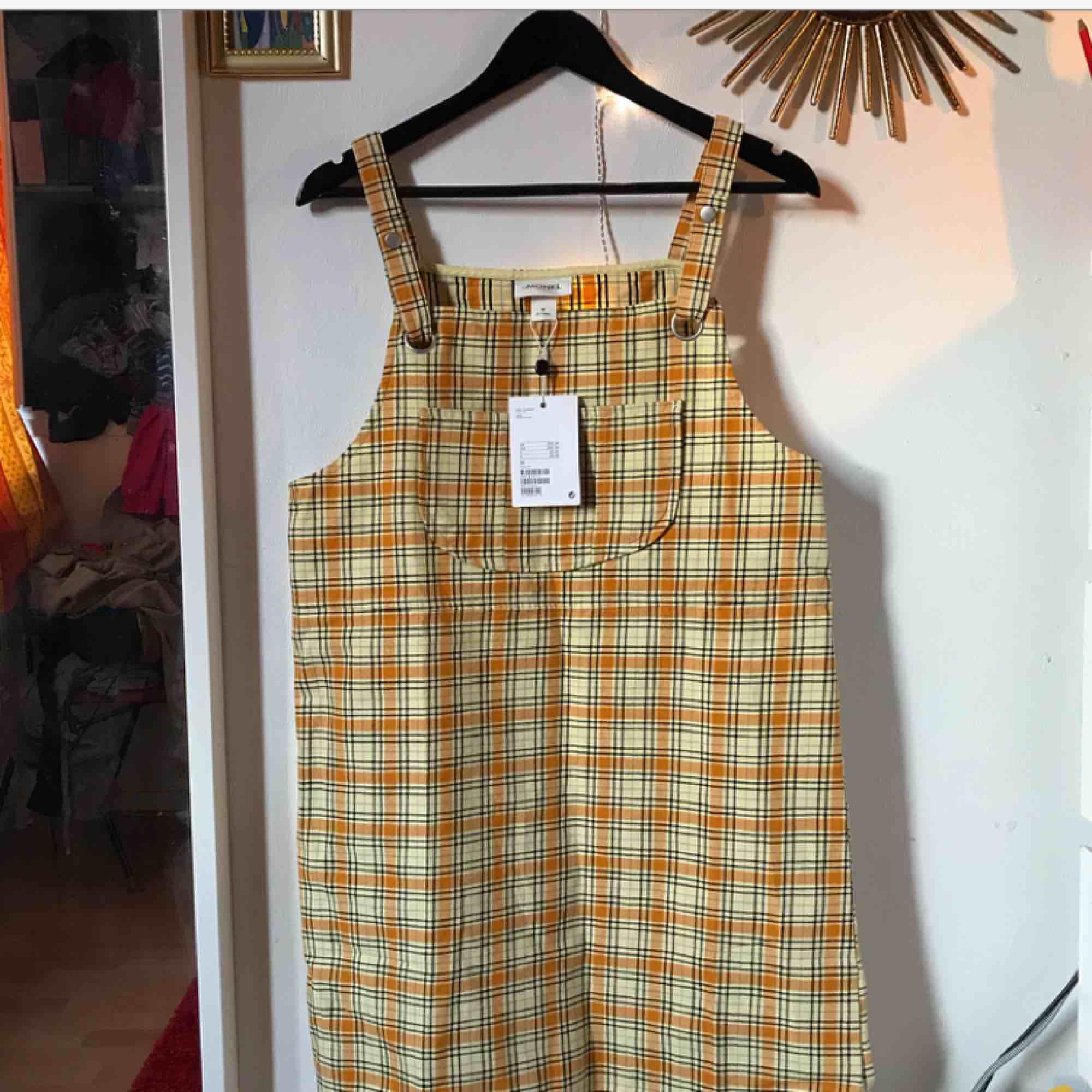 En väldigt fin rutig hängselklänning från Monki. Endast testad med prislappen kvar! Med frakt 200 kronor 🌺🌹🌼. Klänningar.
