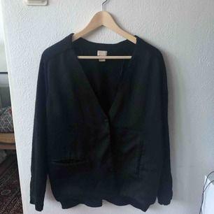 Svart asymmetrisk kofta med silke på framsidan och stickad bomull på baksidan.
