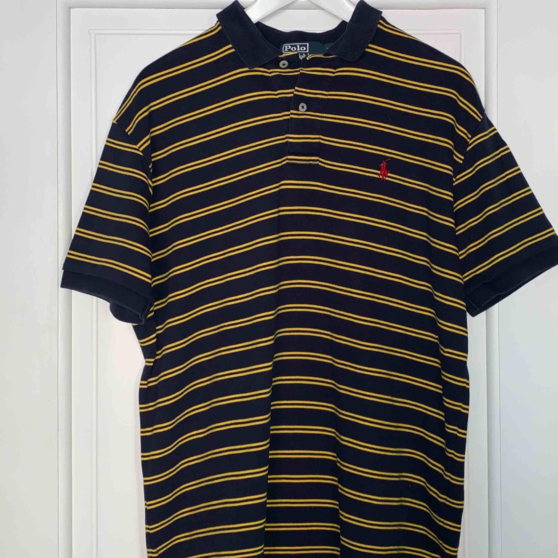 Mörkblå- och gul-randig piké från Ralph Lauren. Väldigt lång i modellen men är väldigt snygg att stoppa in eller klippa av!! . T-shirts.