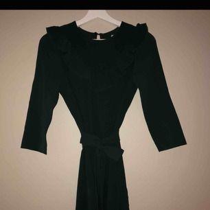 Super fin mörkgrön klänning med volang vid halsen och band i midjan! Oanvänd