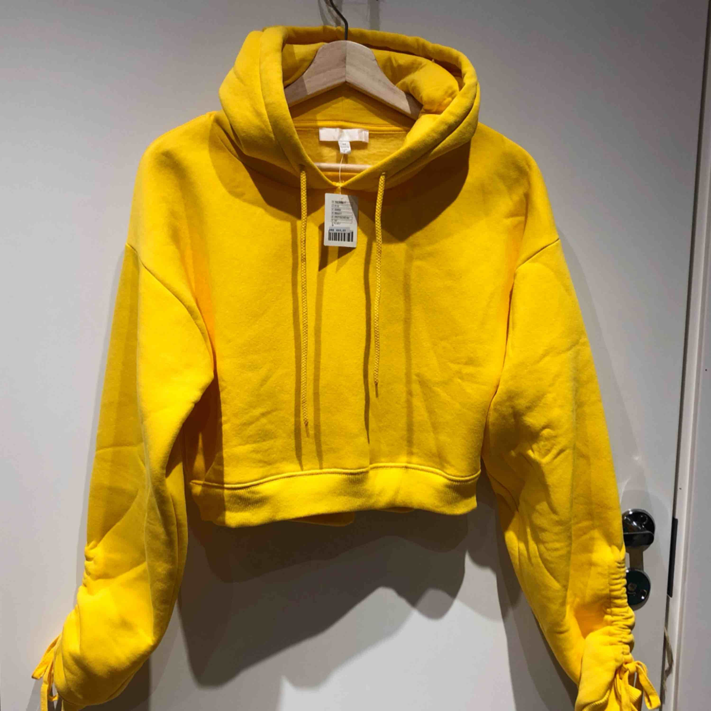 Gul croppad hoodie från urban outfitters. Med supercoola snörningar i armarna! Helt ny, har endast hängt i garderoben och tyvärr inge blivit använd. Mjukt innefoder. Nypris 460 danska (ca 585 svenska). Huvtröjor & Träningströjor.