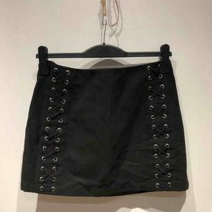 Svart kjol med snördetaljer på framsida i mockaimitation. Sparsamt använd.  Köparen står för frakt