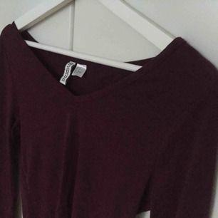 Säljer en vinröd tröja med V-ringning! Tröjan är från H&M och har aldrig använts. Är i storlek M men kan bäras av någon som har S :).