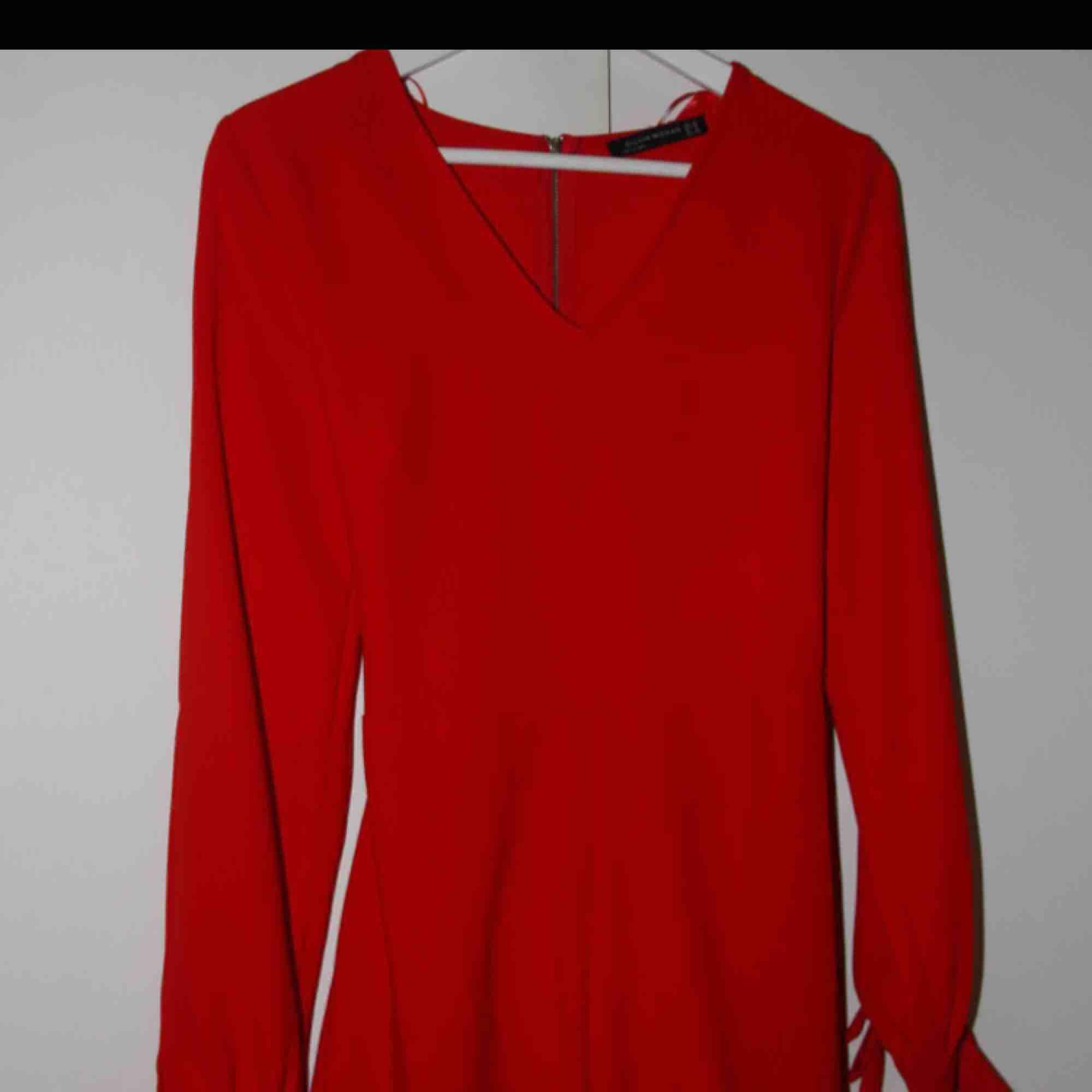Röd/coral färgad jumpsuit från Chiquelle. Använd 1 gång. Storlek 38 (S/M). Öppningar i armarna, en mindre öppning i ryggen och rosett . Övrigt.