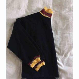Mörkblå tröja med gula och röda detaljer på armar och kragen. Lite polo style på kragen :)