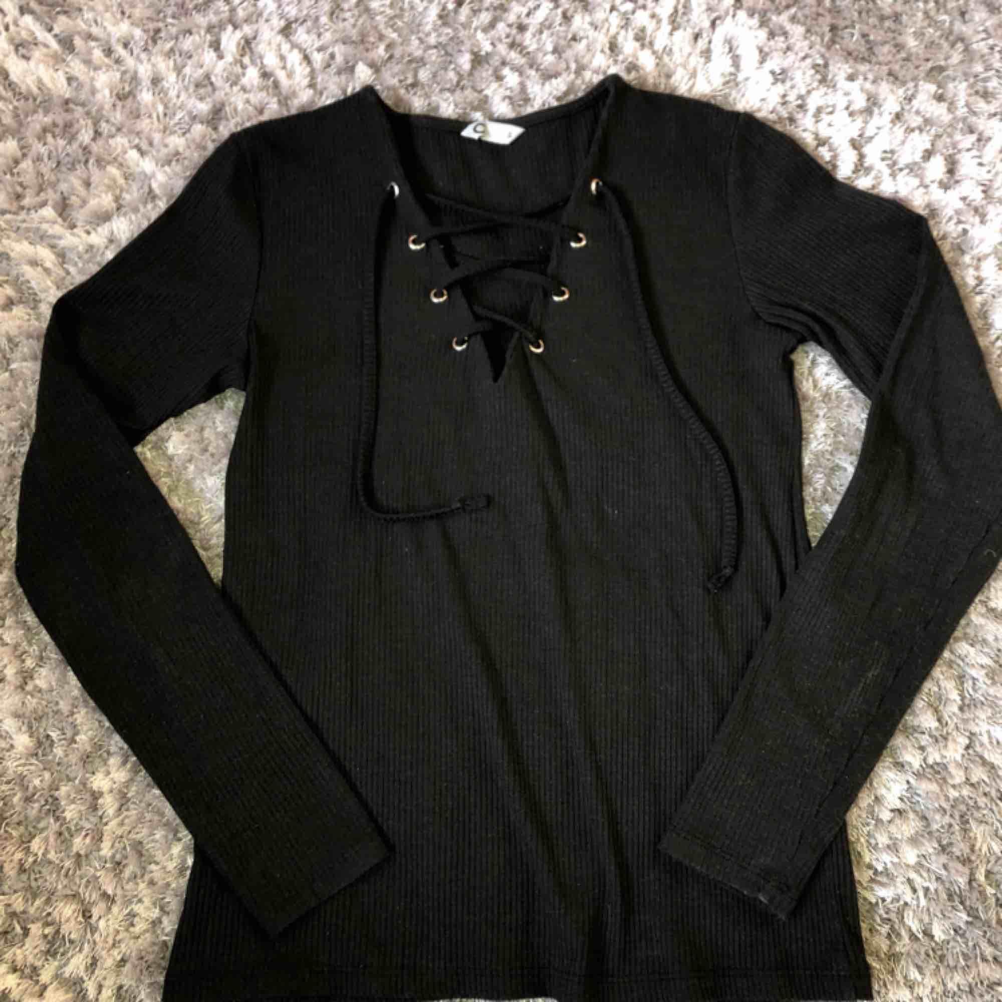 Nypris: 199kr. Storlek S. Knapp använda tröja som jag köpte förra året. Ribbat svart tyg med en snörning framtill.. Toppar.