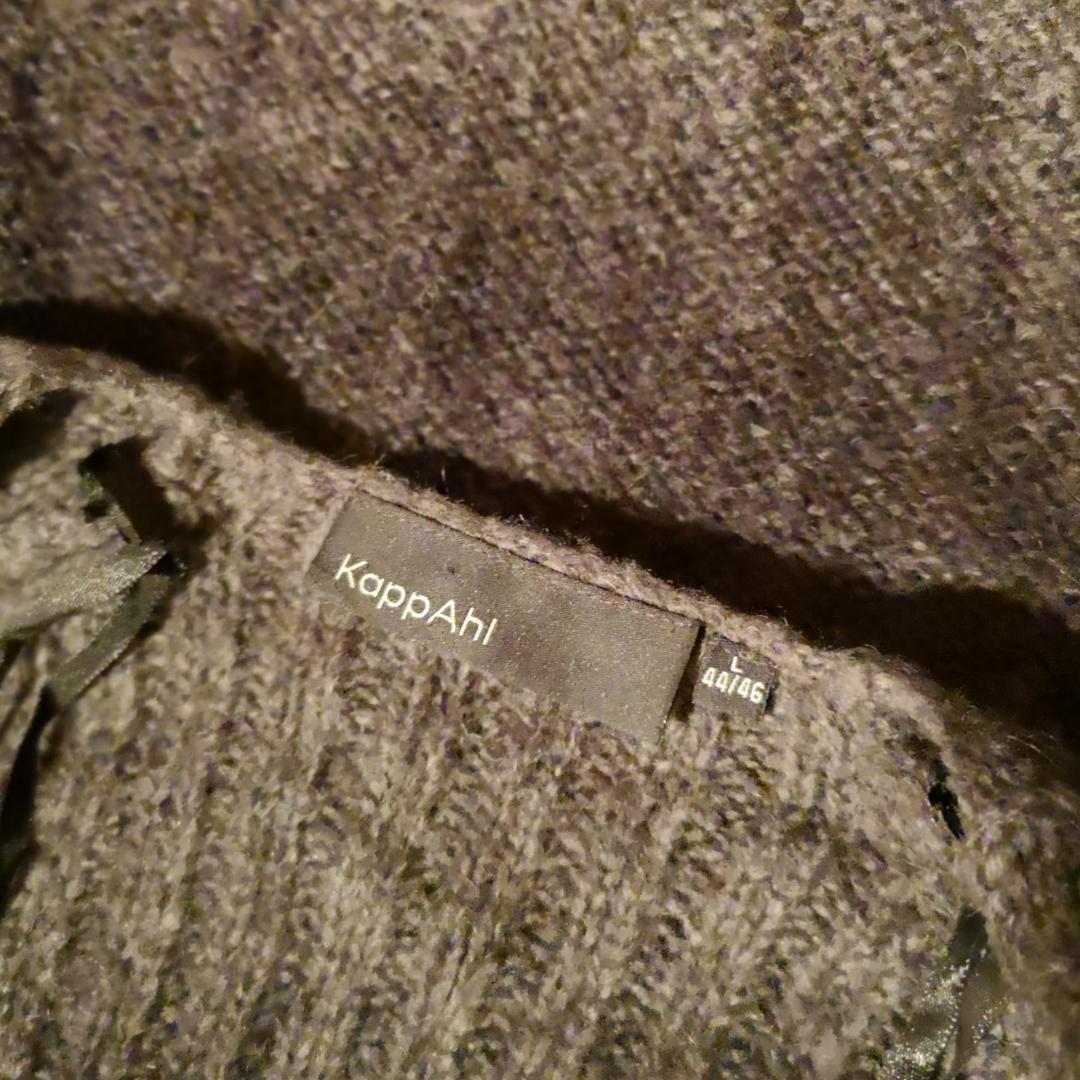 Värmande ullkavaj i grått med vida arm och längre framtill. Den gråa färgen går över i olika toner över plagget och det finns en knäpp-knapp framtill. . Stickat.