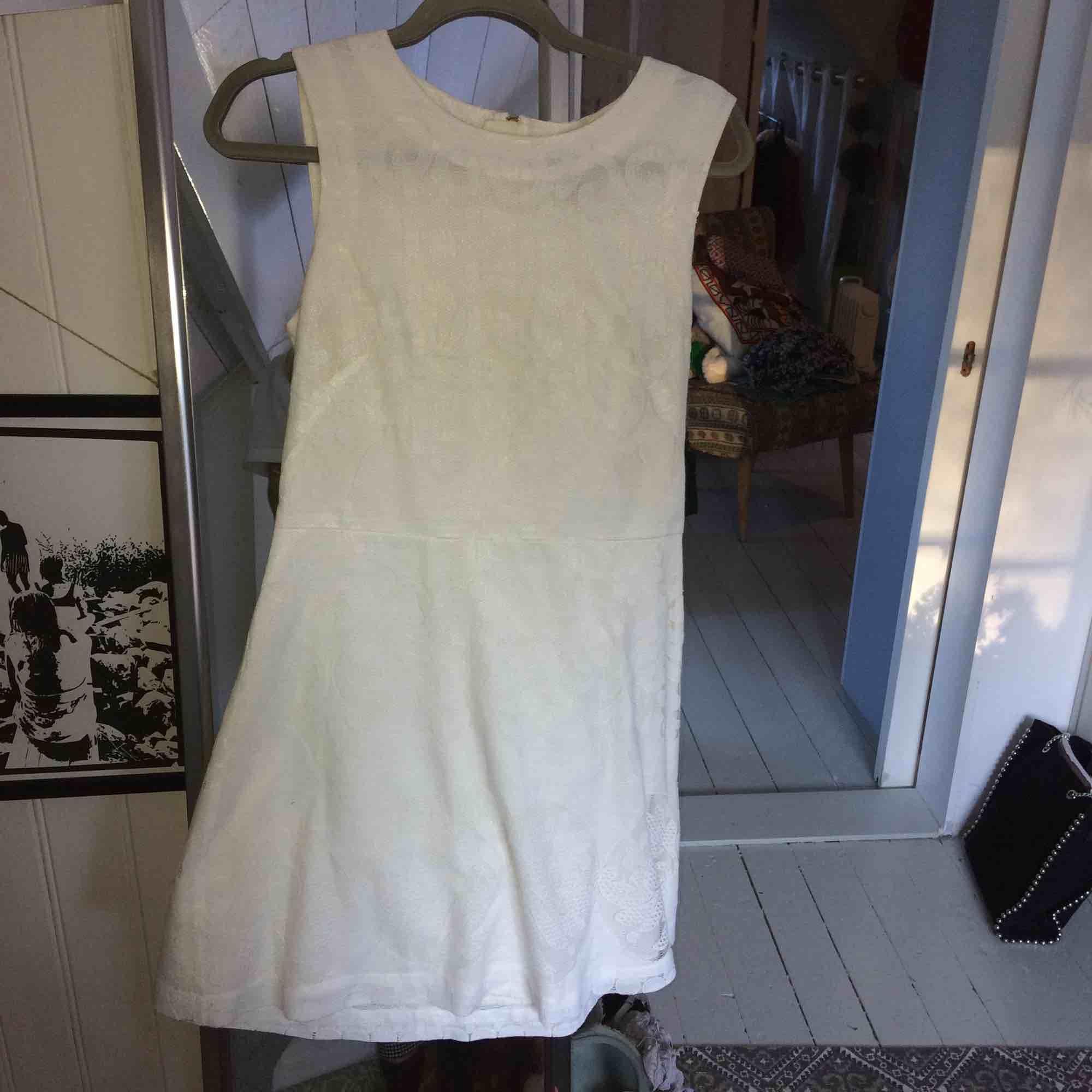 Gräddvit klänning i ett fint mönster med gulddragkedja som går ganska långt ner där bak. . Klänningar.
