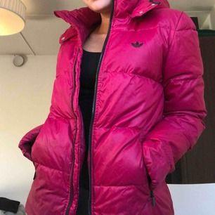 Rosa Adidas dunjacka.  Använd flitigt under en säsong men är ej speciellt sliten.  Avtagbar luva.  Jättevarm och mysig.