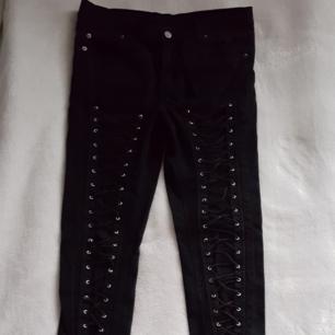 Svarta jeans med snörning längst benen som går att dra åt och justera. Står 31/32 men tycker de är små i storleken, mer som ca 27-28. I fint skick, enda jag kan se är att lappen bak är lite spräcklig. Kan skickas om köparen står för fraktkostnaden.