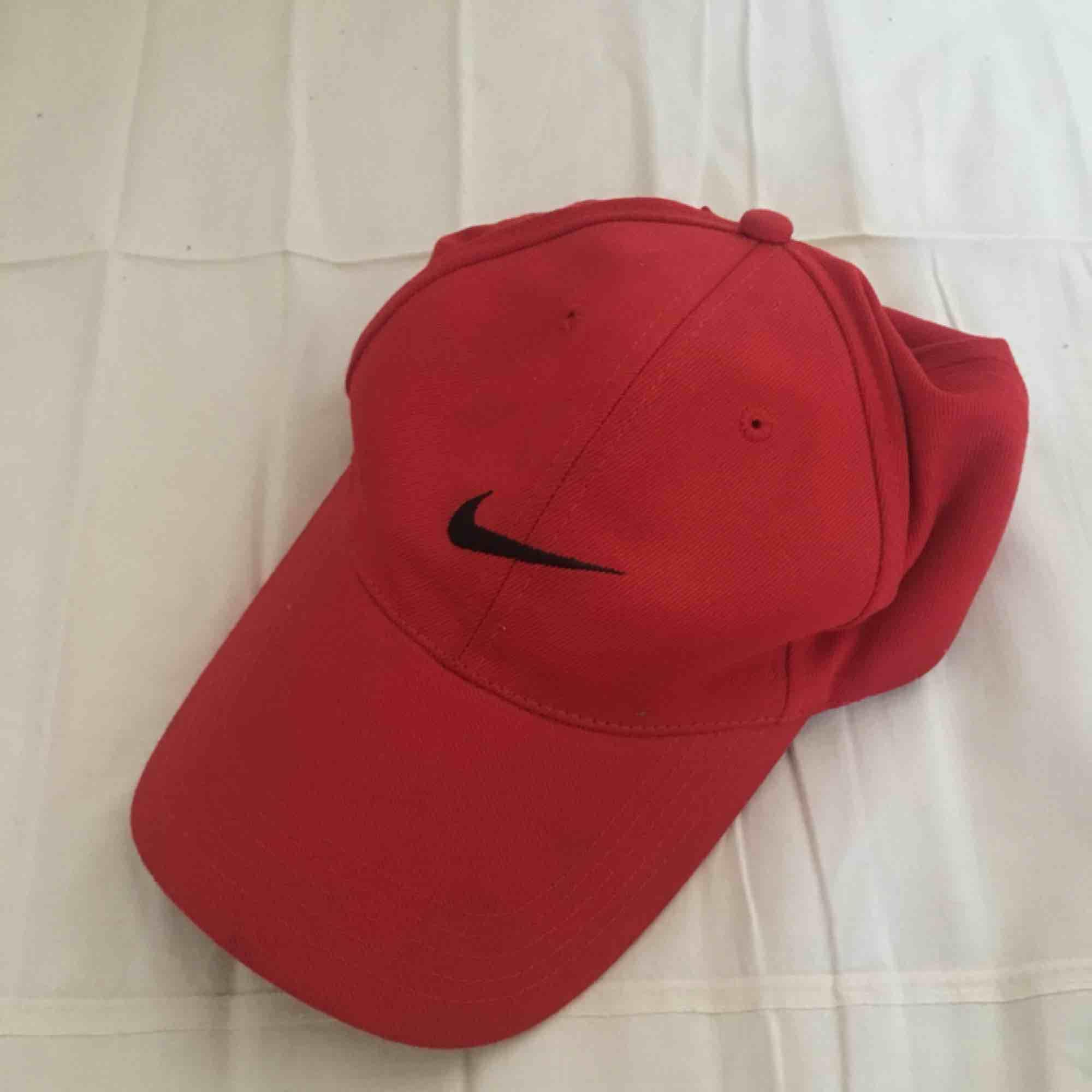 Röd 1990s Nikekeps. I fint, begagnat skick. Ett namn är överstruket på lappen (se bild). Porto på 18 kr tillkommer.😊. Accessoarer.