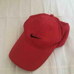 Röd 1990s Nikekeps. I fint, begagnat skick. Ett namn är överstruket på lappen (se bild). Porto på 18 kr tillkommer.😊