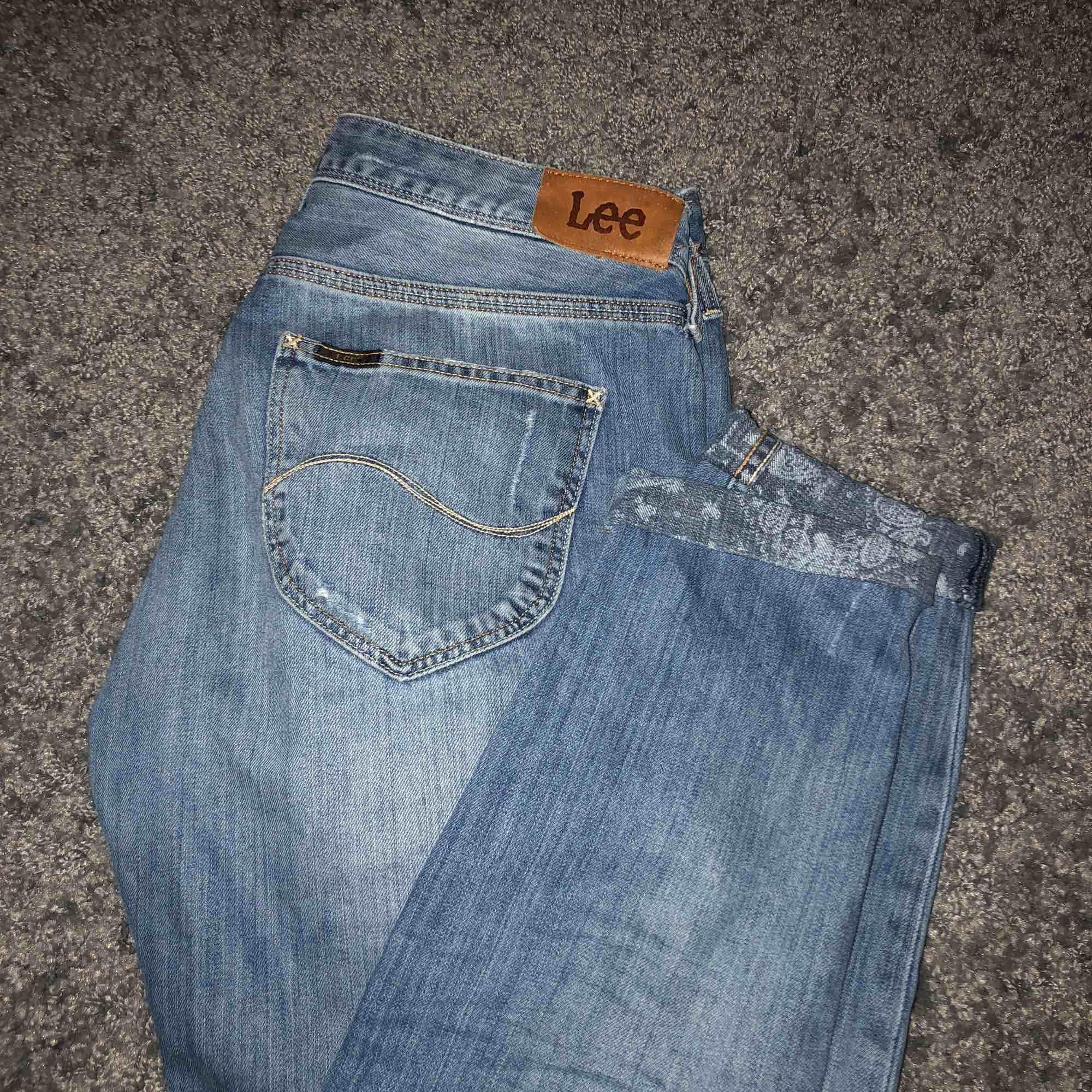Jättefina lee jeans säljes pga de blivit förstora. Jättefint skick och har ovanliga detaljer såsom mönstret nertill av byxorna. Obs skinnlappen med bak har lossnat lite. Men går att fixa! Köparen står för frakt.. Jeans & Byxor.