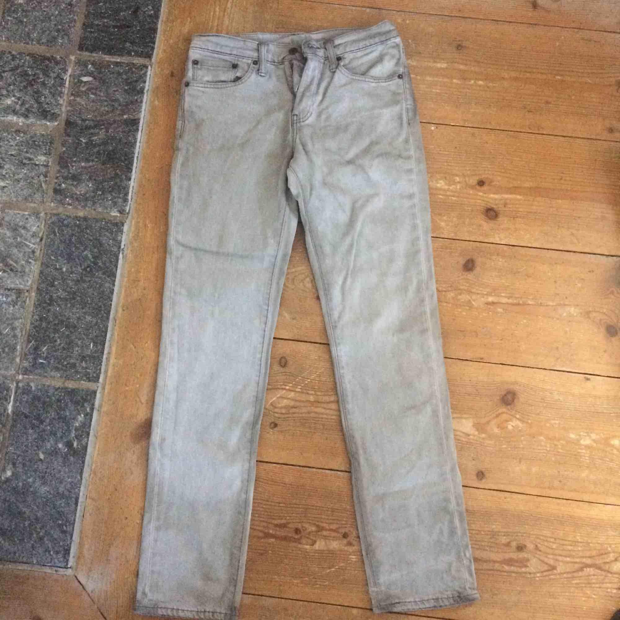 Gråa Levis jeans som är ganska slitna eftersom de är typ missfärgade baktill. . Jeans & Byxor.