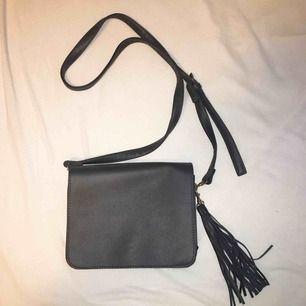 Fin svart väska med tasseldetalj, Väskan har 3 fack. Aldrig använd. Nypris: 299kr. Väskans mått: 20x17cm. FRI FRAKT.