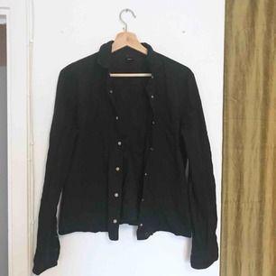 Svart skjorta från Cheap Monday, storlek L men känns mer som en M! Svårt att få på bild, men är små dödskallar i knapparna!