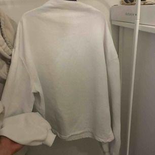 Vit oversize sweatshirt med lite högre krage och lite balong-ärmar ifrån Nelly. Passar XS-M beroende på hur man vill att den ska sitta.