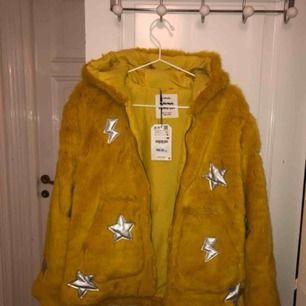Aldrig använd med prislapp kvar! Jättefin gul pälsjacka från zara med stjärnor och blixtrar på. Tyvärr inte min stil. Köpt från barn avdelningen men passar absolut en XS/S