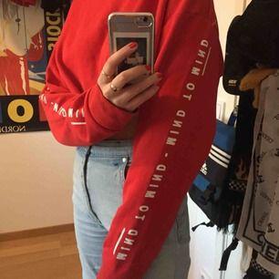 "Röd cropped college tröja. Klippt i nederkanten. Står ""mind to mind"" på båda armarna."