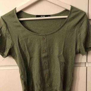 Mörkgrön T-shirt från bikbok som är lite kortare i modellen och har knappar framtill, stl S, använd en gång, säljes pga inte min stil
