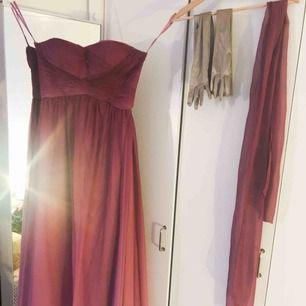 Superfin balklänning i mörkrosa som övergår till ljusrosa! Använd endast en gång, storlek M men rymlig över byst. Köptes för 2000 kr i butik. Champagnefärgade handskar och sjal i samma tyg ingår i pris. Frakt står köparen för!
