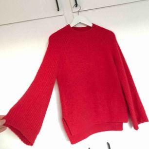 Mysig stickad tröja med vida ärmar. Färgen är röd. Knappt använd, helt i nyskick!