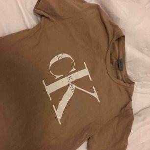 Beige/brun t-shirt från Calvin Klein, max använd 2 gånger så helt i ny skick. Snyggt tryck på bröstet och dom klassiska dubbla sömmarna i ryggen.