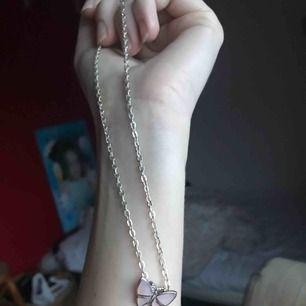Jättefint halsband med silverkedja och en ljusrosa fjäril. Ganska kort kedja, rekommenderar till barn😊 Aldrig använt