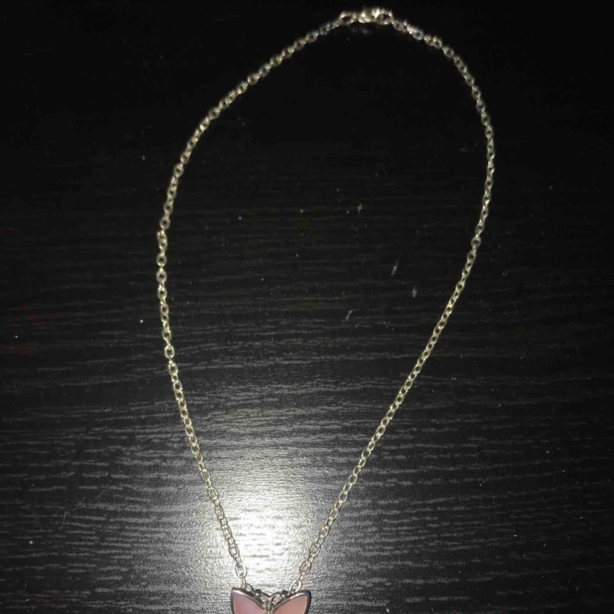 Jättefint halsband med silverkedja och en ljusrosa fjäril. Ganska kort kedja, rekommenderar till barn😊 Aldrig använt . Accessoarer.