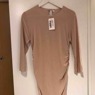 Säljer en oanvänd klänning från nelly. Storleken är XL, men skulle säga att den passar allt från en s till större. Tyget är väldigt stretchigt. Fint veckad på sidorna som gör att den faller fint på kroppen.